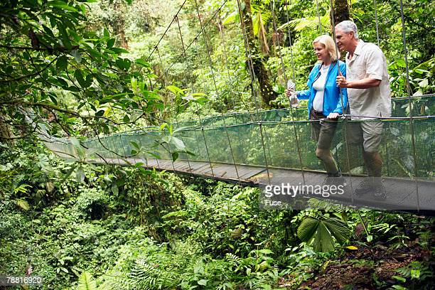 Mature Couple on Rope Bridge in Wilderness Area