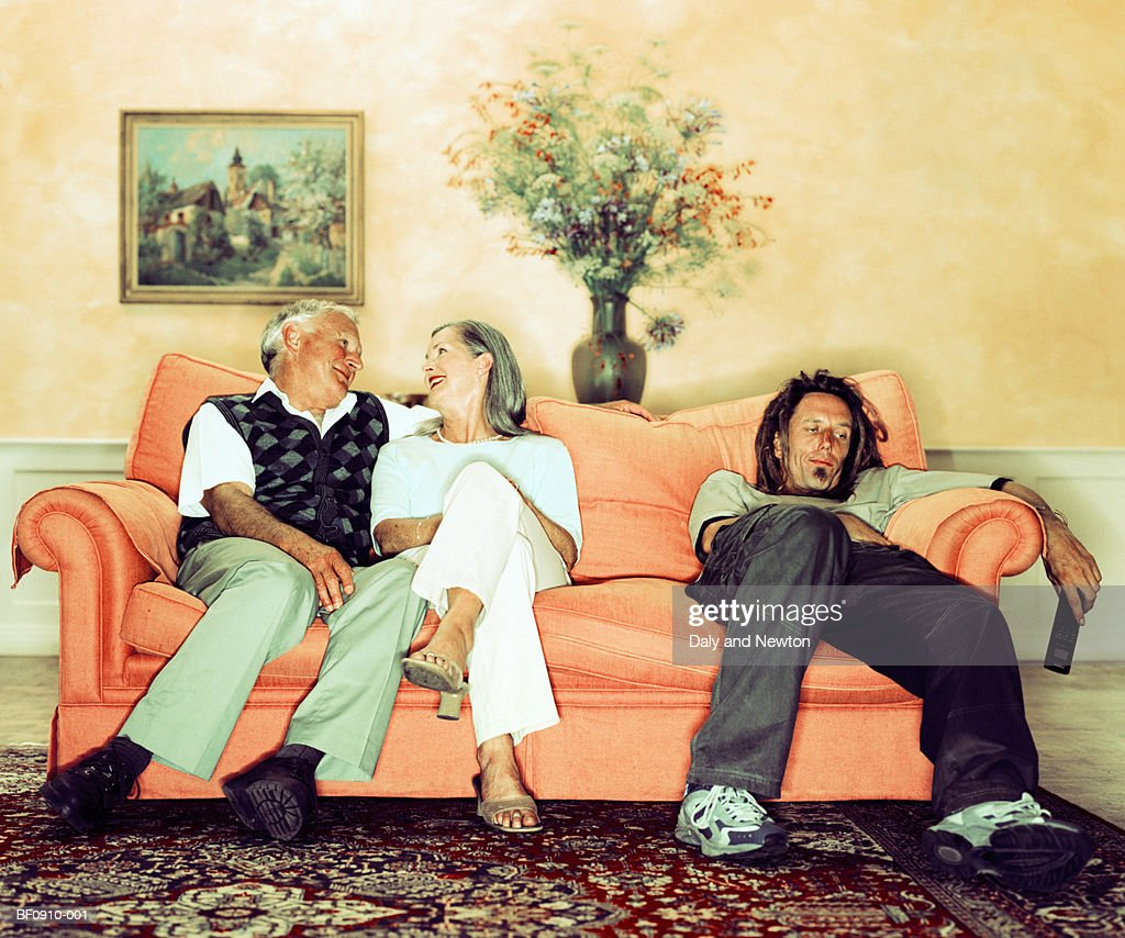 Mature couple on sofa beside man holding television remote