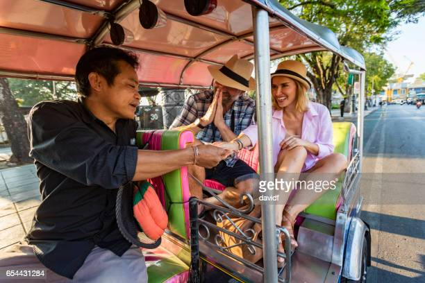 Mature Couple on Vacation Respectfully Paying Tuktuk Transport Driver in Thailand