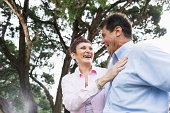 Mature couple (50s, Hispanic / Native American) standing outdoors, laughing.