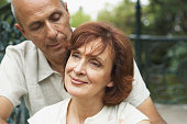 Mature couple outdoors, woman smiling, close-up