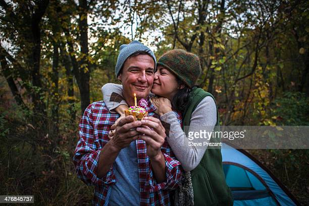 Mature couple outside tent holding birthday cupcake
