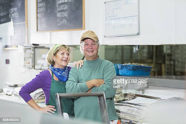 Mature couple, owners of fish market