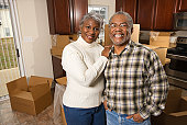 Portrait of senior African-American couple in kitchen with moving boxes.