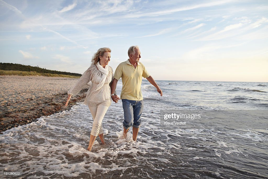 Mature couple paddling in sea looking at sunset : Stock Photo