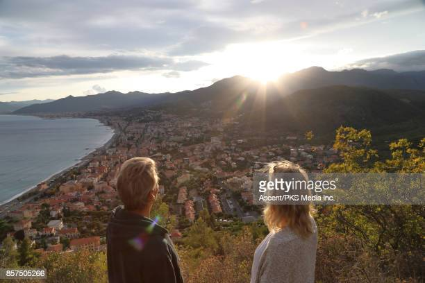 Mature couple pause on mountain slope above sea, village