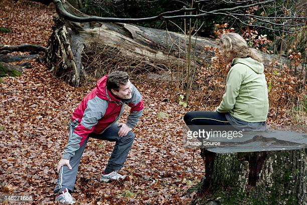 Mature couple performing warming up exercises in forest