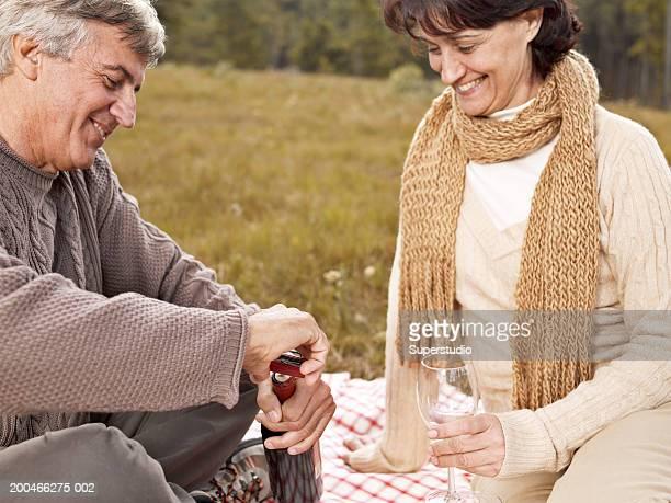 Mature couple picnicking, man opening wine bottle