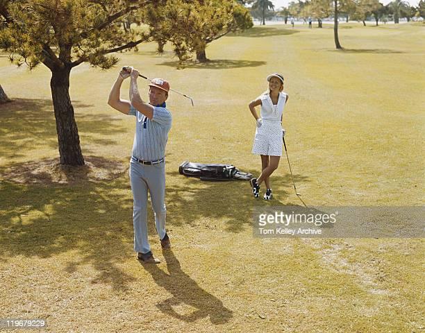 Mature couple playing golf, man swinging golf club