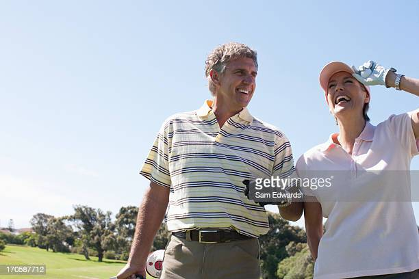 Mature couple playing golf together