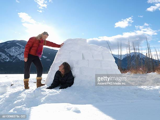 Mature couple playing in igloo on snow covered lake, smiling