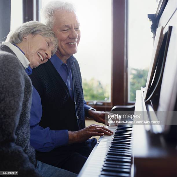 Mature couple playing piano, woman rests her head on man's shoulder