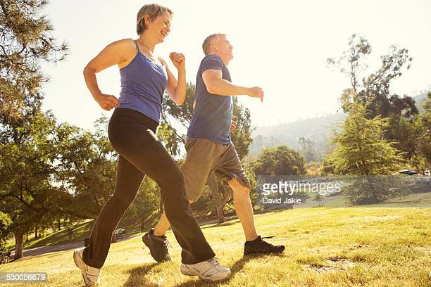 Mature couple power walking in park
