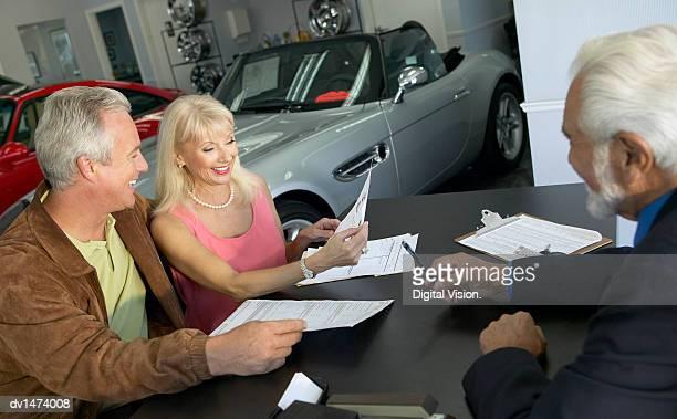 Mature Couple Read a Document as a Car Salesman Passes Them a Pen