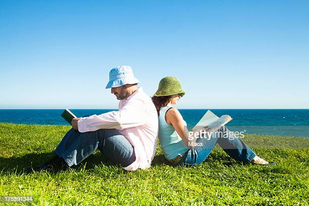 Mature couple reading by the sea