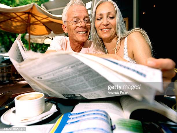 Mature couple reading newspaper at outdoor cafe, smiling