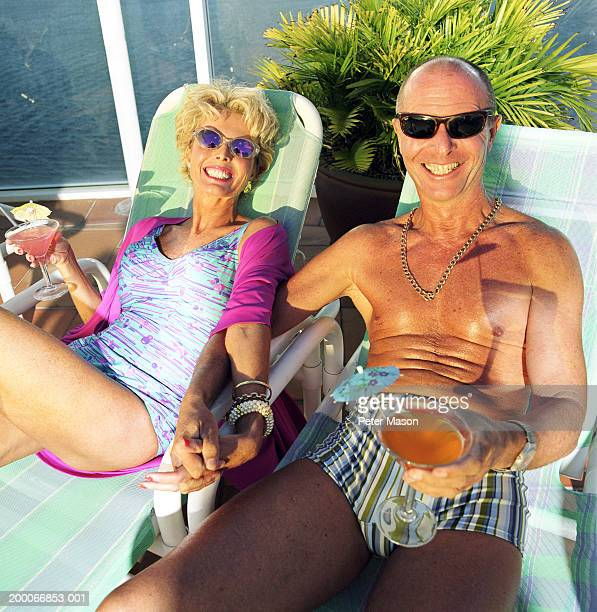 Mature couple reclining on sun loungers, portrait, elevated view