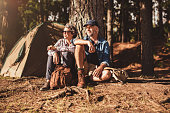 Portrait of senior couple sitting together under a tree in forest and looking at a view. Mature man and woman relaxing at their campsite.