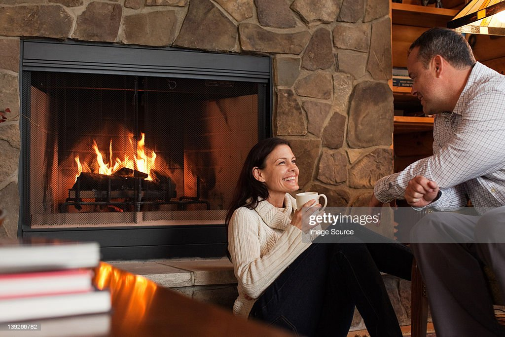 Mature couple relaxing by fireplace