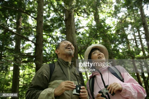 Mature couple relaxing in a park, low angle view : Stock Photo