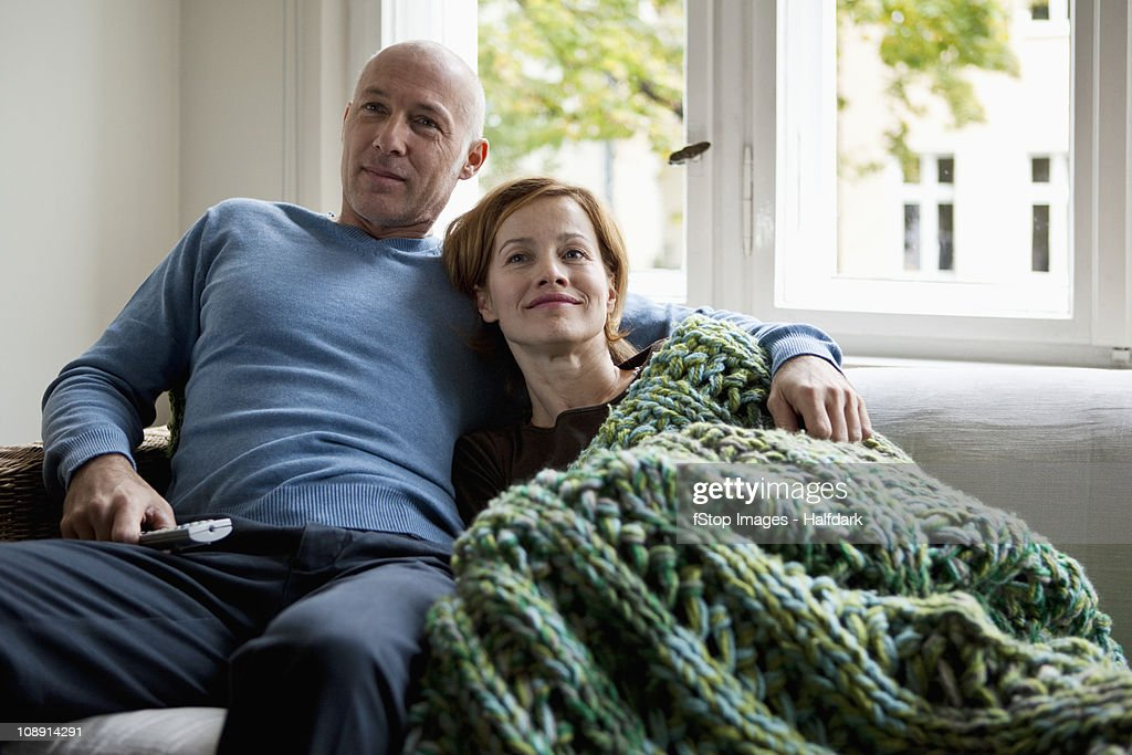 A mature couple relaxing on a sofa