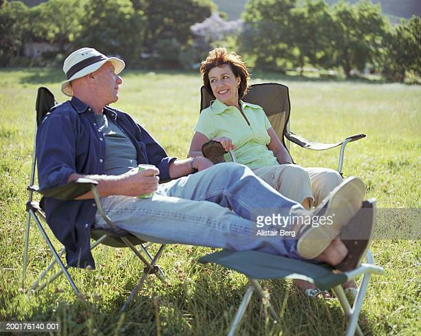 Mature couple relaxing on folding chairs in field