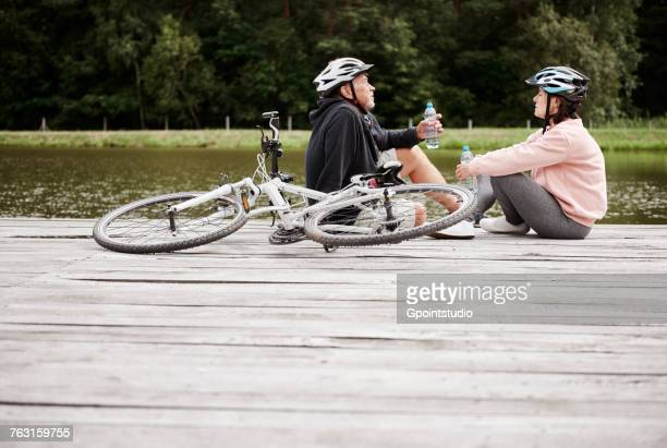 Mature couple relaxing on jetty beside lake, bicycles behind them