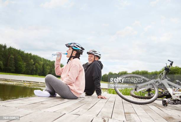 Mature couple relaxing on jetty, bicycles beside them