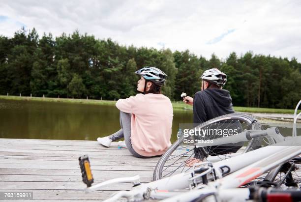 Mature couple relaxing on jetty, bicycles beside them, rear view