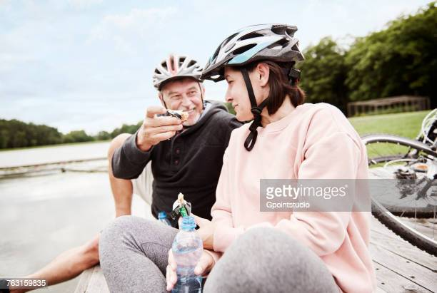 Mature couple relaxing on jetty, enjoying snack, bicycles behind them