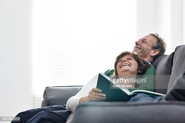 Casal relaxante no sofá com um livro