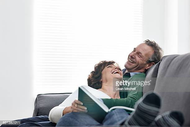Mature couple relaxing on sofa with a book smiling