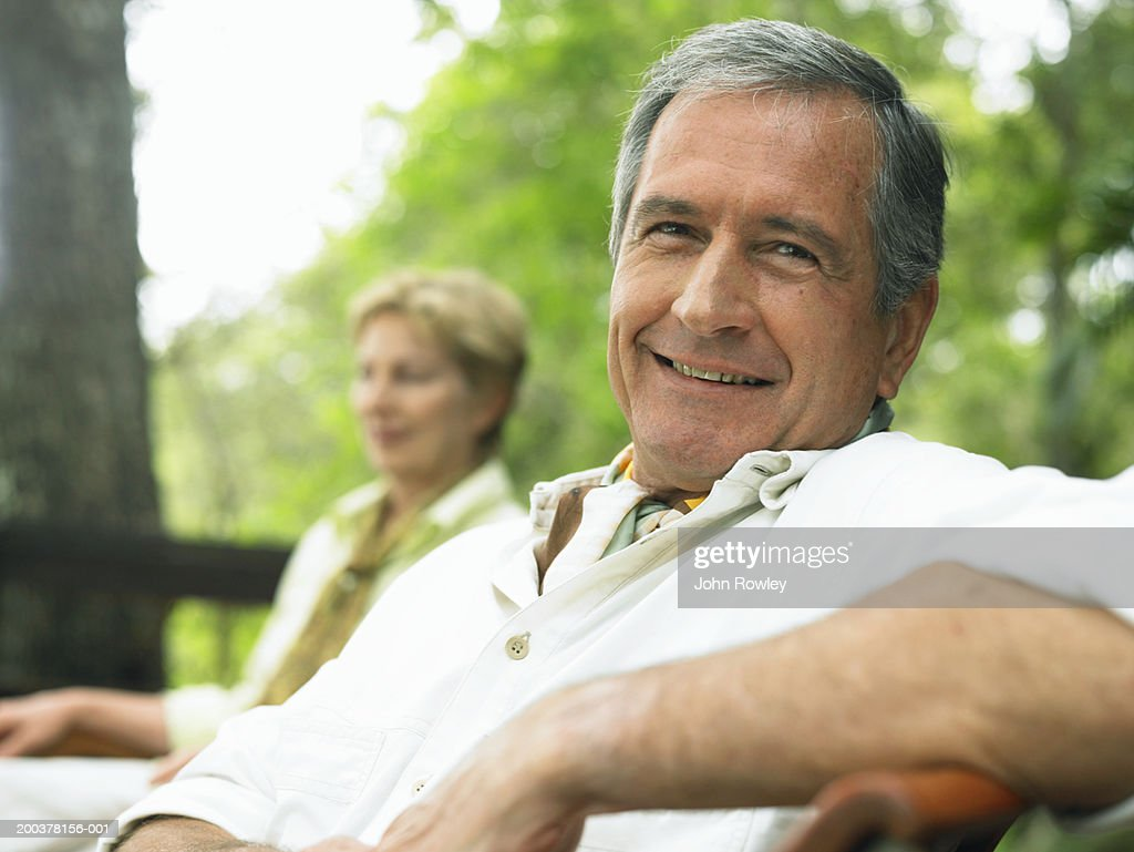 Mature couple relaxing outdoors, man, smiling, close-up : Stock Photo