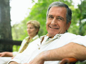 Mature couple relaxing outdoors, man, smiling, close-up