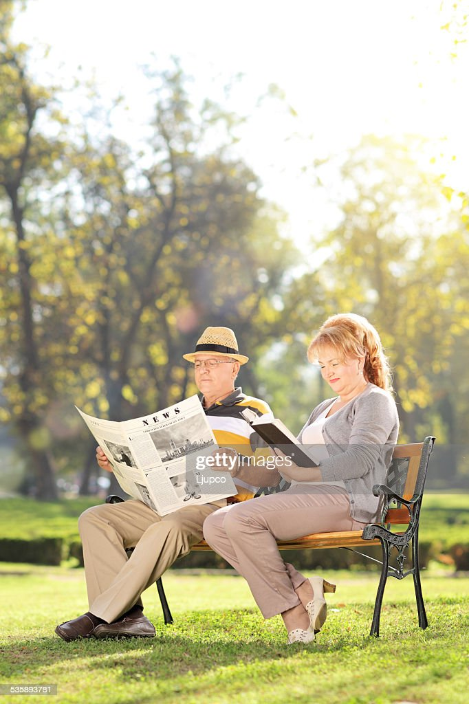 Mature couple relaxing seated on a bench in park : Stock Photo