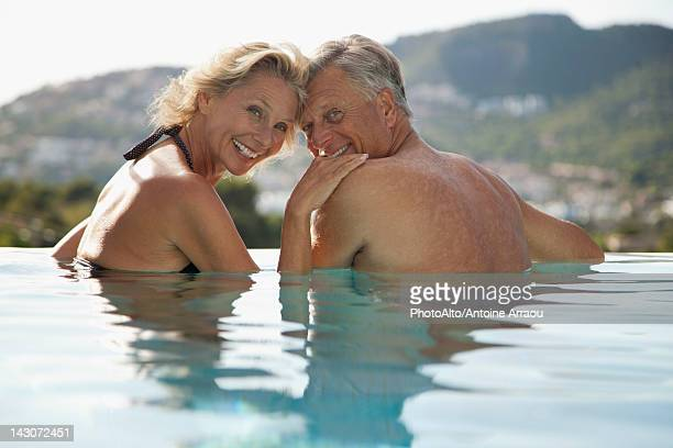 Mature couple relaxing together in pool