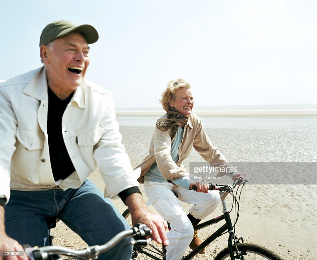 Mature couple riding bicycles on beach : Stock Photo