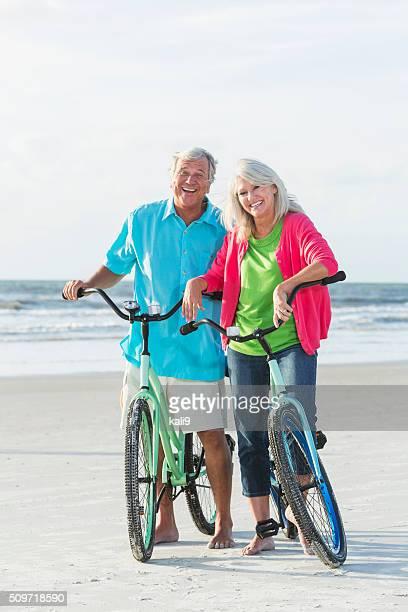 Mature couple riding bikes on the beach