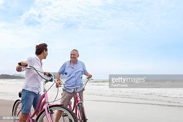 Bicicletas de equitação Casal maduro ao ar livre na praia ao pôr do sol