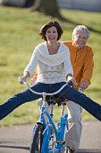 Mature couple (50-60) riding tandem bike