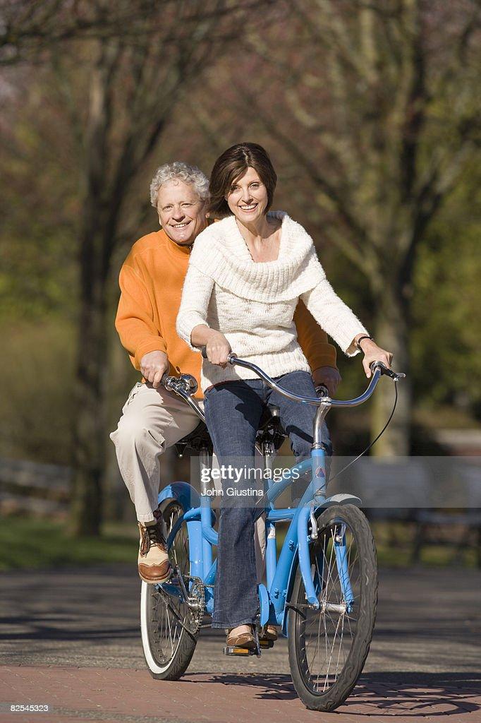 Mature couple (50-60) riding tandem bike : Stock Photo