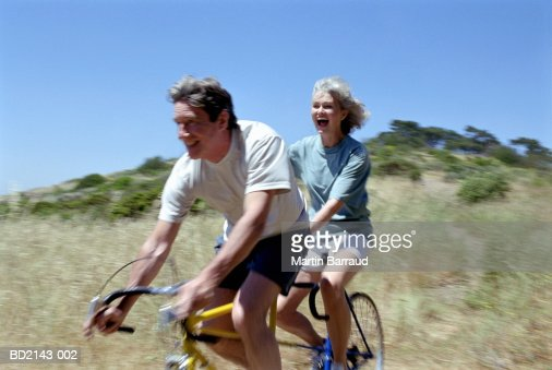 Mature couple riding tandem, smiling (blurred motion) : Foto de stock