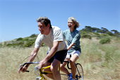 Mature couple riding tandem, smiling (blurred motion)