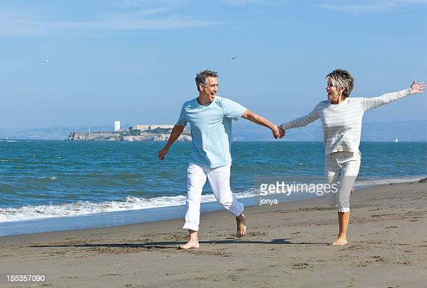 mature couple running along the beach