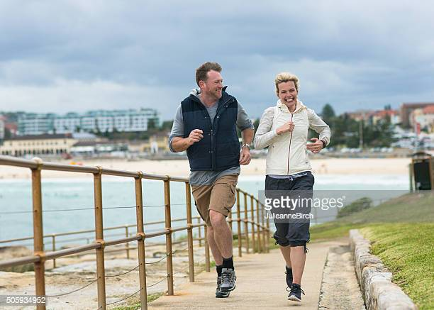 Mature couple running, Bondi Beach