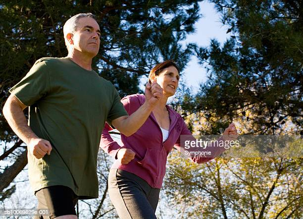 Mature couple running in park, low angle view