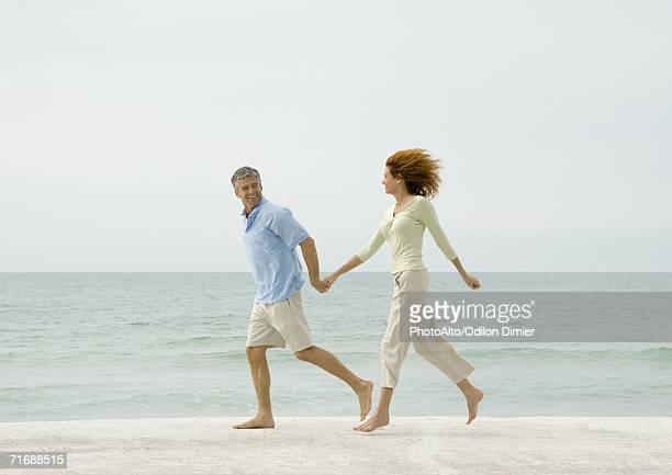 Mature couple running on beach