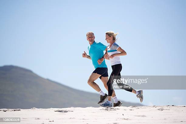 Mature couple running on beach together