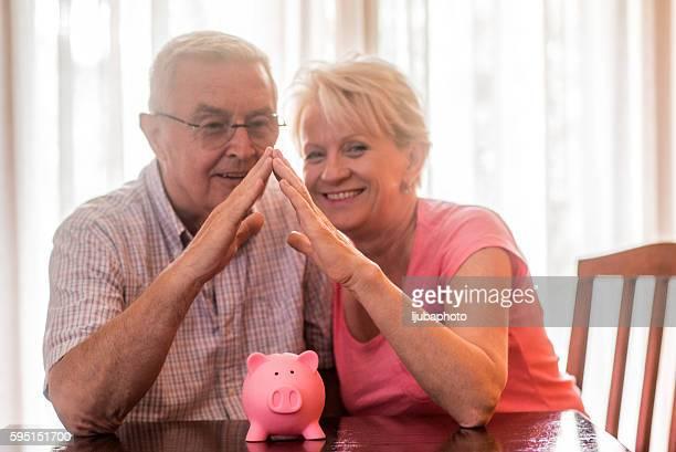 Mature couple saving money in piggybank at home