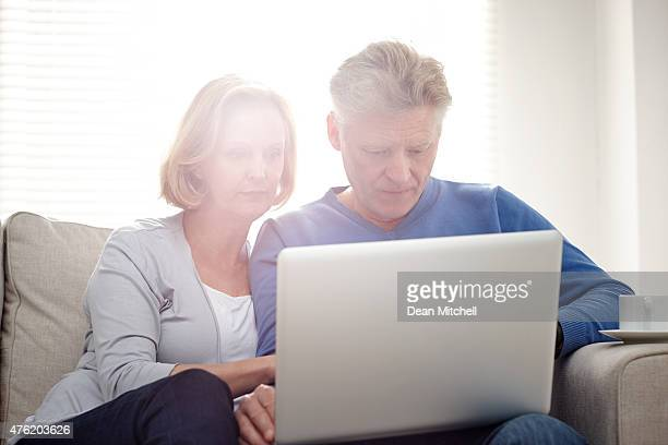 Mature couple seriously working on laptop